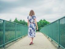Woman walking on footbridge in country Royalty Free Stock Photos