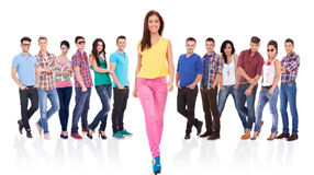 Woman walking forward in front of a large team Royalty Free Stock Image