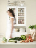 Woman Walking By Fresh Produce On Kitchen Counter Royalty Free Stock Photos