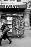 Woman walking in front of French press kiosk Stephen Hawking dea. PARIS, FRANCE - MAR 15, 2018: Senior man buying French newspaper Liberation at Parisian press Royalty Free Stock Photo