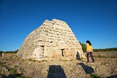 Woman walking in front of prehistoric monument Royalty Free Stock Photos