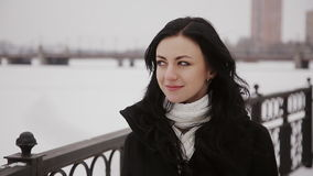 Woman walking on a frozen winter river bridge. Beautiful young woman  passes the river on a snowy bridge stock video