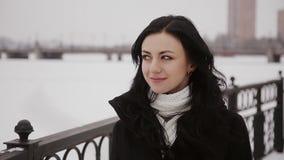 Woman walking on a frozen winter river bridge stock video