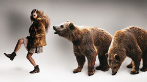 Woman walking in fur coat with two bears Stock Photo
