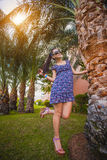 Woman is walking in the garden with palm trees Royalty Free Stock Images