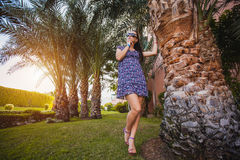 Woman is walking in the garden with palm trees Stock Photo