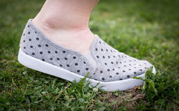 Woman is walking in grass, shoe with dots Stock Photos