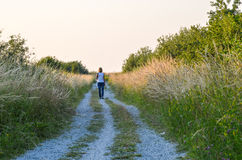 Woman walking at a gravel road at summer Royalty Free Stock Image