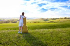 Woman walking in green field with acoustic Guitar stock images