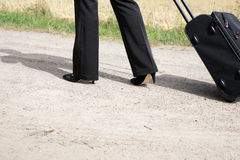 Woman walking with hand luggage suitcase Stock Images