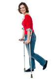 Woman walking with the help of crutches royalty free stock photo
