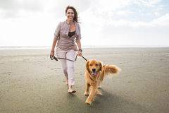 Woman walking her dog. A pretty woman with bare feet walking her golden retriever dog on a sandy beach Royalty Free Stock Photography