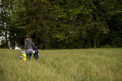 Woman walking her two children through a field Royalty Free Stock Images