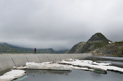 Woman walking on high mountain dam wall in a cold sullen day Stock Images