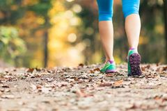 Woman walking and hiking in autumn forest. Sport shoes. Jogging, trekking or training outside in autumn nature. Inspiring health and fitness concept Royalty Free Stock Photos