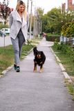 Woman walking with his female small mixed breed dog on leash, posing in front of camera. Portrait of lady, owner and half breed. Woman walking with his female royalty free stock photo