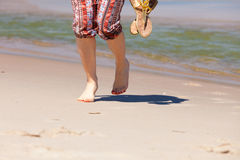 Woman walking holding flip flops Stock Images