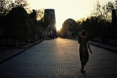 Woman walking home in the sunset in the historical walled city of the silk road stock photography