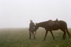 Woman walking horse in fog Royalty Free Stock Image