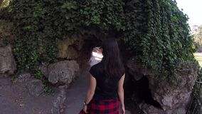 Woman Walking Inside Cave. Young Attractive Caucasian Woman Walking Path Inside Cave Hole With Lake, Trees And Fountain In Buen Retiro Park, Madrid, Spain stock video
