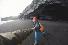 Woman walking on Kirkjufjara black sand beach, southern Iceland. Happy smiling woman traveler with small orange backpack walking on Kirkjufjara black sand beach Royalty Free Stock Photos