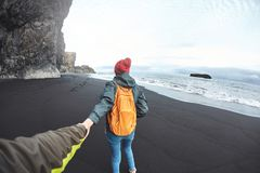 Woman walking on Kirkjufjara black sand beach, southern Iceland. Happy smiling woman traveler with small orange backpack walking on Kirkjufjara black sand beach Royalty Free Stock Photography