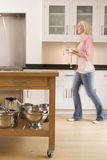 Woman walking in kitchen holding coffee Stock Image