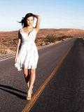 Woman Walking the Line. Young Adult Asian woman walks down the center yellow line of a desert roadway.  Model is wearing short white light weight dress.  Casual Stock Images