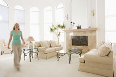 Woman walking through living room stock photo