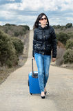 Woman Walking in Lonely Road with Suitcase Royalty Free Stock Photo
