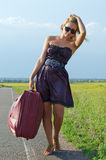 Woman walking with luggage in the country Royalty Free Stock Image