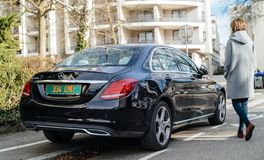 Woman walking luxury Mercedes-Benz E220d diesel car royalty free stock photos
