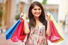 Woman Walking Through Mall Carrying Shopping Bags Royalty Free Stock Photos