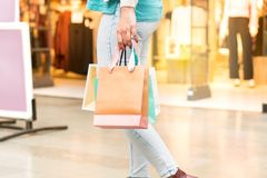 Woman walking at a mall carrying shopping bags. Stock Photos