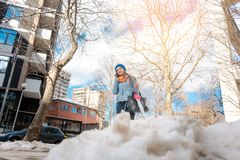 Woman walking through melting snow in late winter stock photo