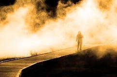 Woman Walking Through Misty Steam on Boardwalk Stock Image