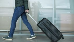 Woman is walking in modern airport terminal carrying suitcase, closeup legs. Traveler woman in jeans and lacket is walking in modern airport terminal carrying stock video footage