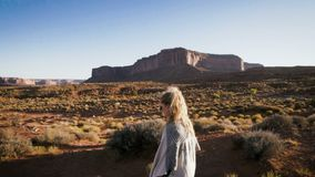 Woman walking in Monument Valley with red rocks overview. stock video footage