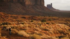 Woman walking in Monument Valley with red rocks overview. stock footage