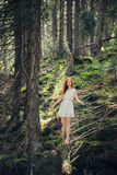 Woman walking in the mystery forest. Fairytale woman walking on the fallen tree in the mystery mountain forest Stock Photos
