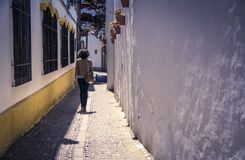 Woman walking in a narrow old street in Ronda, Andalusia, Spain. Woman walking in a narrow old street with typical flowerpots and Flowers on a white walll Stock Image