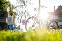 Woman walking near bicycle in urban area Stock Photos