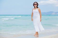 Woman walking near blue sea. Royalty Free Stock Photo