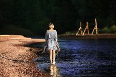 Woman Walking Near Body of Water Stock Images