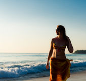 Woman walking near the sea at sunset Royalty Free Stock Photo