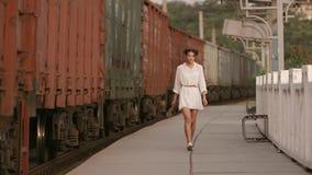 Woman walking near train rail on train station. Beauty, freedom, summer travel concept. stock video