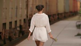 Woman walking near train rail on train station. Beauty, freedom, summer travel concept. stock footage