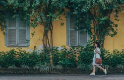 Woman Walking Near Trees Beside Yellow House royalty free stock photography