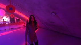 Woman walking in neon underground lights. Young woman walking confidently in dark loft club with bright neon flashing lights. A cheerful girl smiles and looks at stock video footage