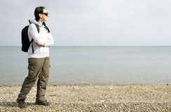 Woman walking next to the sea on pebble beach Stock Photography